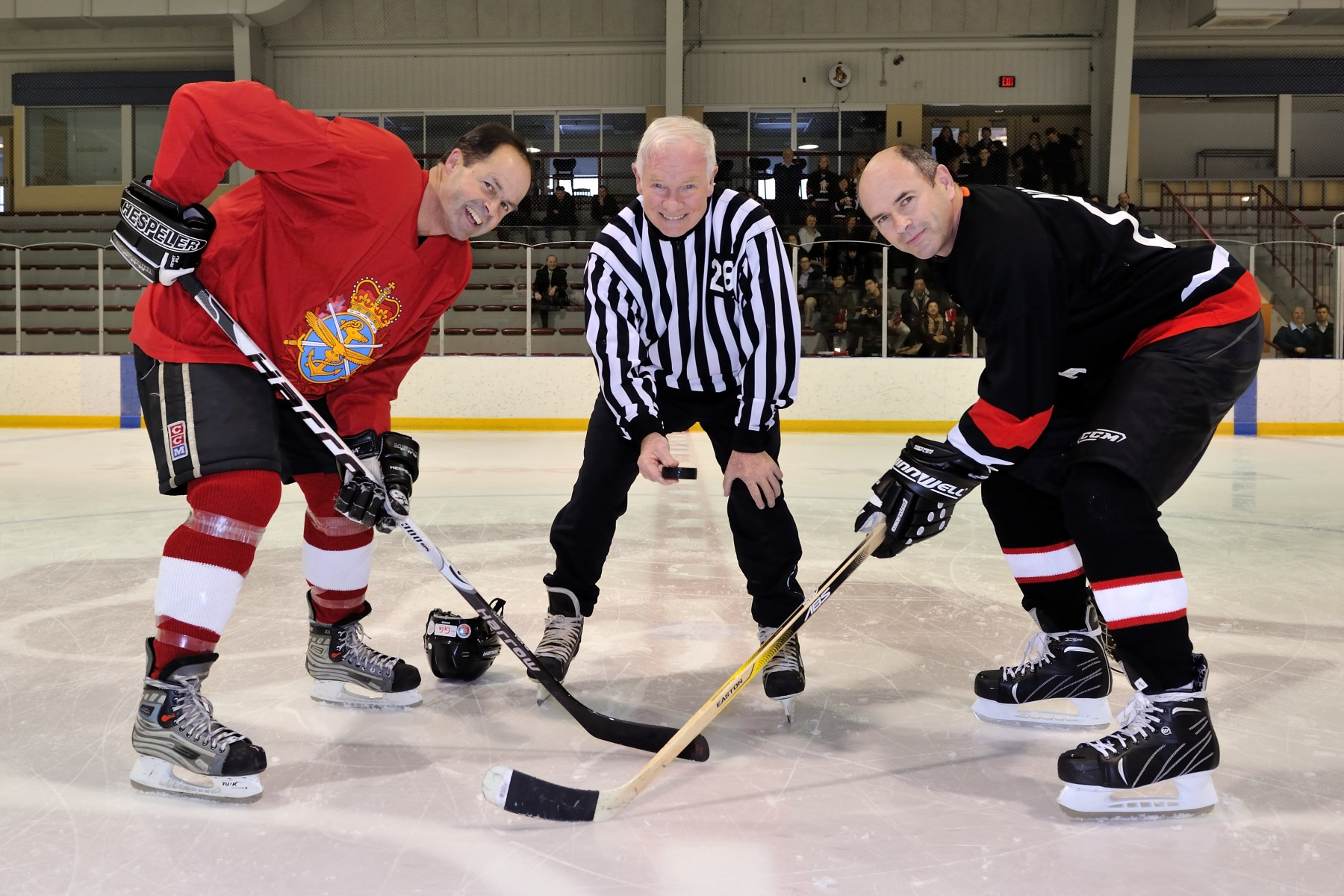 His Excellency conducted the official puck-drop with captains from both teams: Chief of the Defence Staff General Tom Lawson of the GOFO team (left), and Captain (N) Ramino Navajas (right) of the Lame Ducks team.