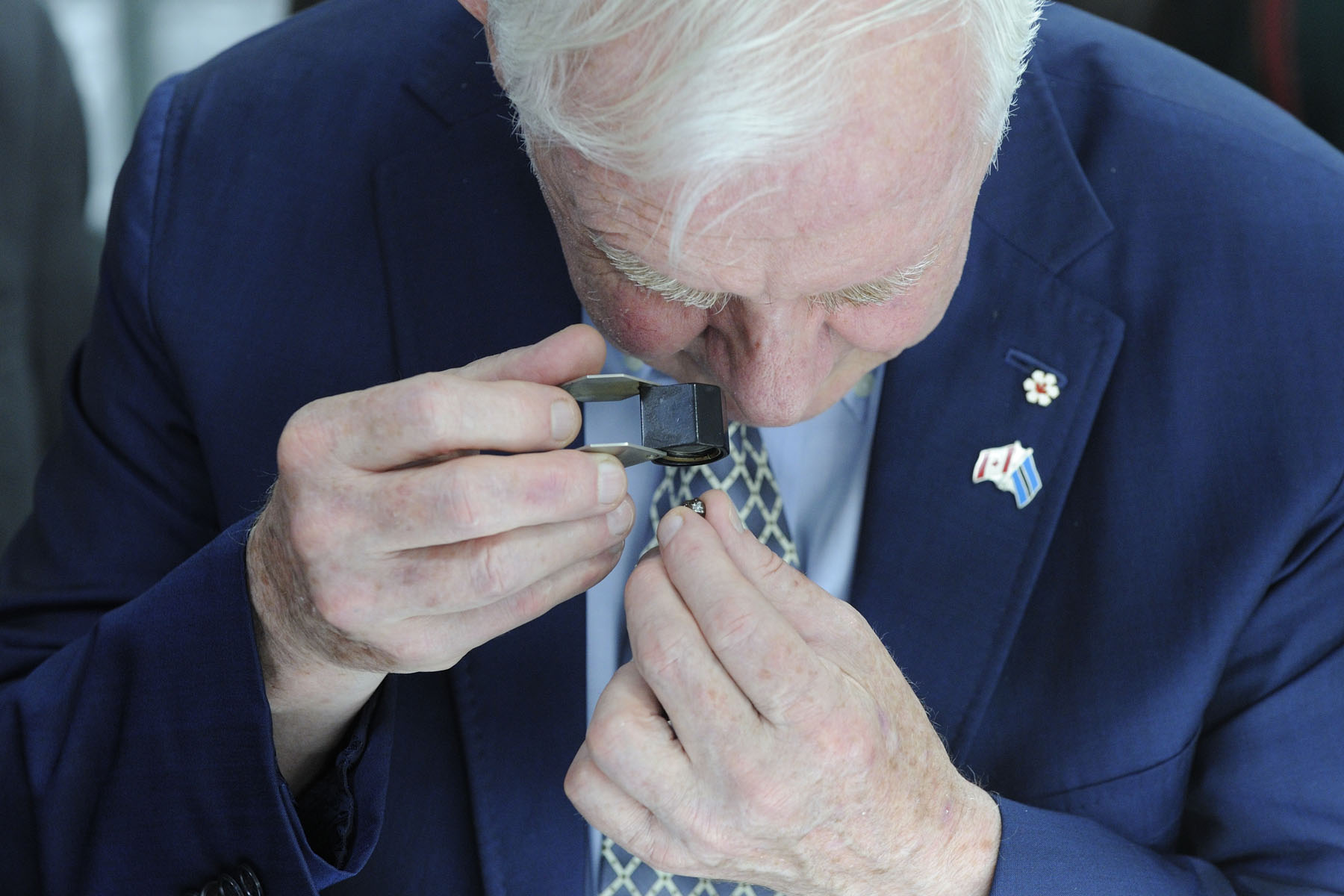 His Excellency inspected a diamond with a jeweler's loupe.