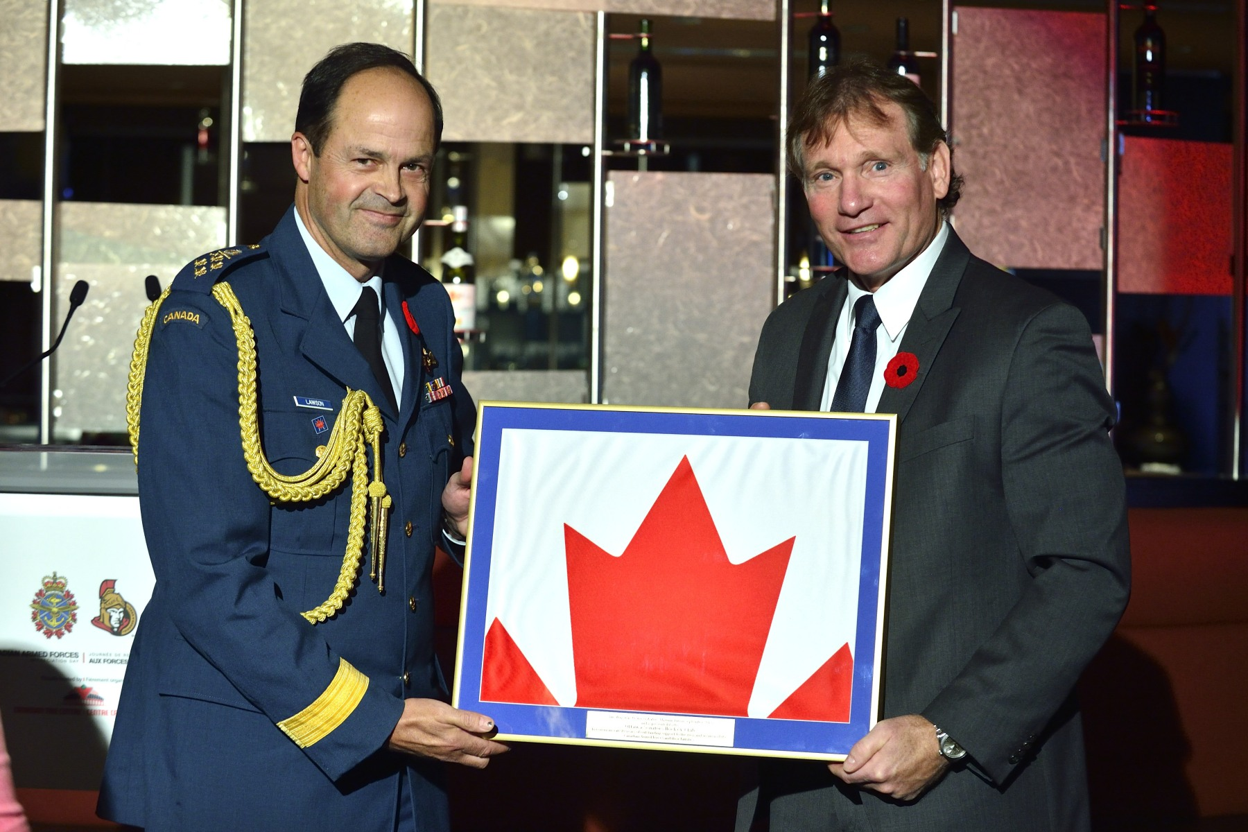 General Tom Lawson presented the Canadian flag that was flown in Kandahar, Afghanistan, to Mr. Cyril Leeder, President of the Ottawa Senators.