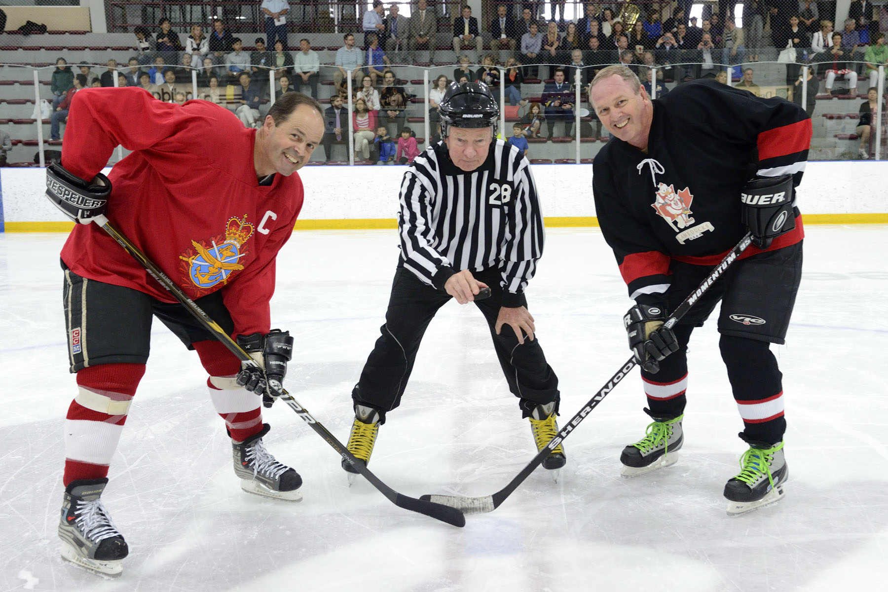 His Excellency conducted the official puck-drop with captains from both teams: Chief of the Defence Staff General Thomas J. Lawson of the GOFO team (left), and Wing Commander Russell Page (right) of the Lame Ducks team.