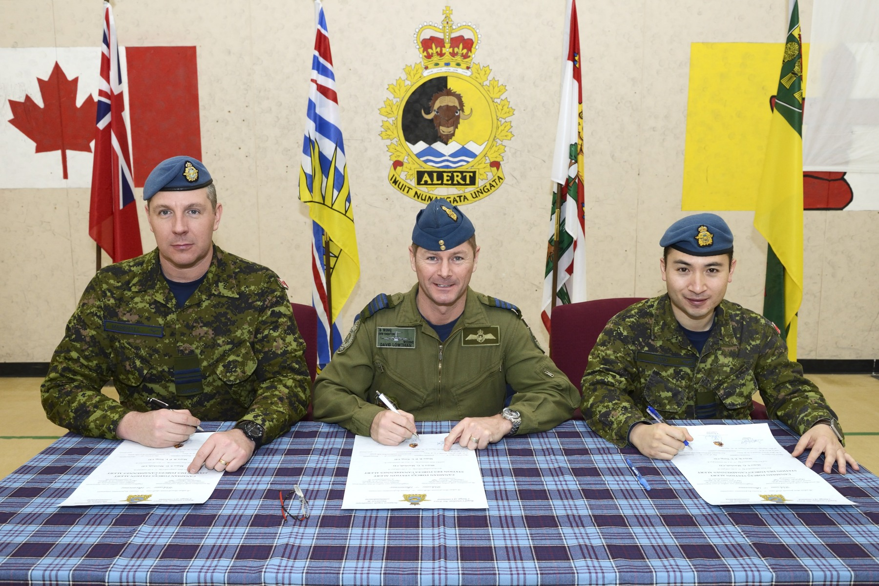 The outgoing Commanding Officer of CFS Alert, Major Scott Marshall (left), the Presiding Officer, Colonel David Lowthian (middle) and the incoming Commanding Officer of CFS Alert, Major Brian Tang (right) signed the scroll.