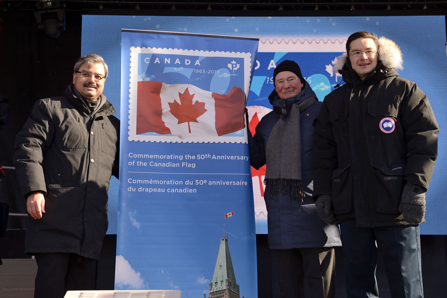 Along with Mr. Deepak Chopra, President and CEO of Canada Post (left) and Mr. Pierre Poilievre, Minister responsible for the National Capital Commission (right), the Governor General unveiled a new stamp commemorating the 50th anniversary.