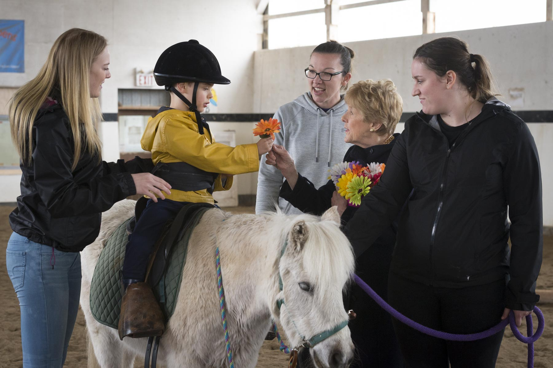 In the riding class, students collected flowers and offered them to Mrs. Johnston. Pride Stables provides a safe, high-quality riding program for persons with disabilities.