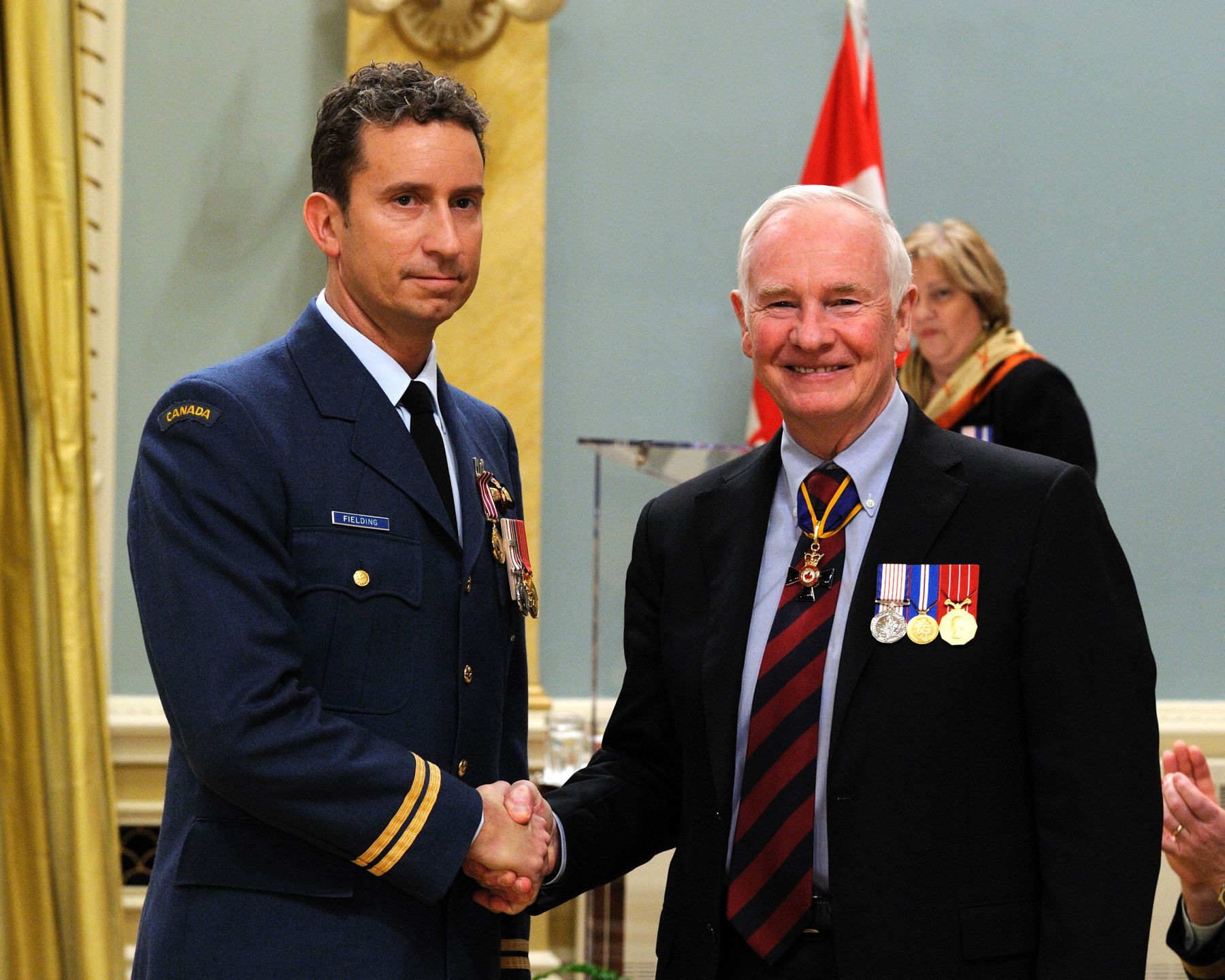 Captain William Todd Fielding, M.M.V., C.D., received the Medal of Military Valour from His Excellency. On August 5, 2010, Captain Fielding's Chinook helicopter was struck by enemy fire, in Panjwaji, Afghanistan, causing the fuel tank to explode and rendering the aircraft nearly inoperable. With the helicopter in flames and the cockpit rapidly filling with smoke, Captain Fielding made the time-critical decision to land in enemy territory rather than fly to a friendly landing zone.  His outstanding courage and devotion to duty allowed him to execute an emergency landing and then lead the evacuation of the burning aircraft. His actions no doubt saved the lives of all crew and passengers that day.