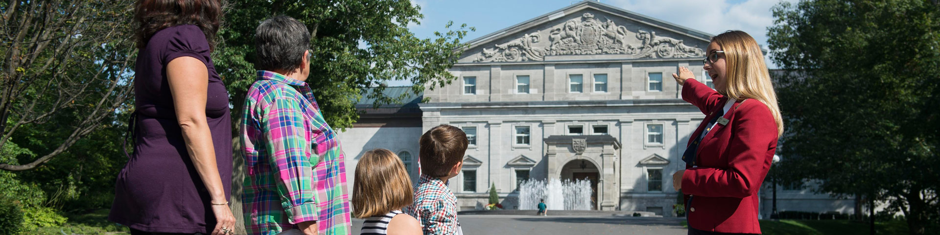 A guide-interpreter showing Rideau Hall Residence façade (and its fountain) to a small group of visitors.