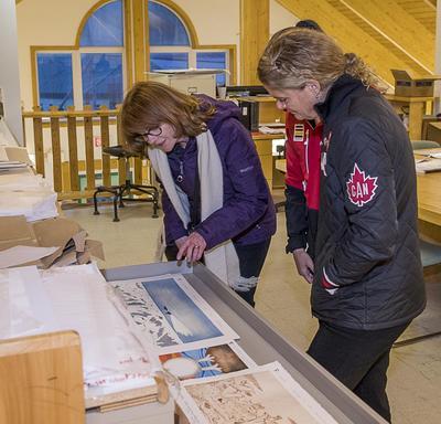 Son Excellence qui contemple les impressions de paysages de l'Arctique canadien dessiné par des artistes locaux.