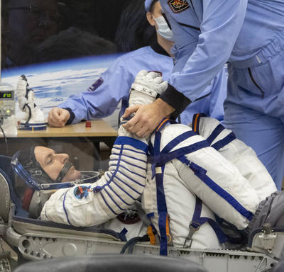 David Saint-Jacques is in his space suit and is crouched into a seat.  He is being examined by a man in a light blue jumpsuit and face mask prior takeoff.