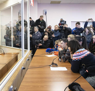 David Saint-Jacques is seated in front of a microphone.  He is separated from the crowd by large glass windows.  The crowd is composed of Governor General, Julie Payette, family members and media.