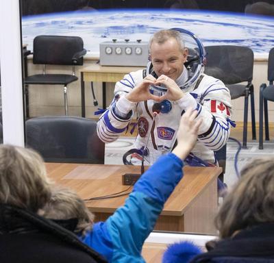 David Saint-Jaques fait un coeur avec ses mains.  Il est assis derrière le verre de quarantaine et porte sa combinaison spatiale.
