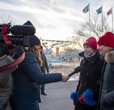 The Governor General, Julie Payette, and Véronique Morin, spouse of astronaut David Saint-Jacques are being interviewed.   A female journalist hold a microphone towards them while they are filmed by a large hand held camera.