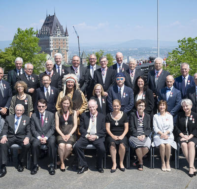 Newly invested members of the Order of Canada take a group photo with the Governor General.
