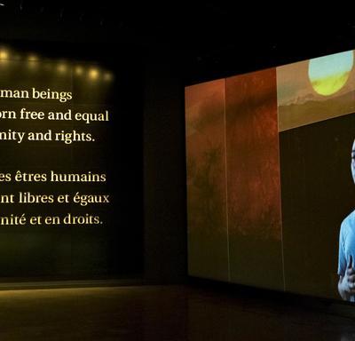 """Sur un mur, une vidéo joue, sur un autre mur, les mots « Tous les êtres humains naissent libres et égaux en dignité et en droits"""" sont écrits »."""