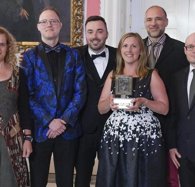 A group of 5 people representing the Telegraph-Journal are posing with Governor General Julie Payette who is at the extreme left. A lady in the middle is holding the Michener Award trophy.