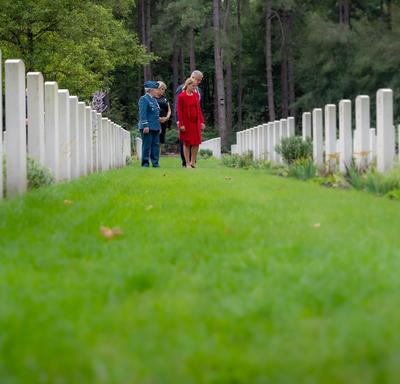 The Governor General looks intently at tombstones at the Bergen-op-Zoom Canadian War Cemetery.