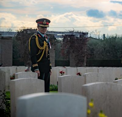 The Governor General walks through a cemetery.