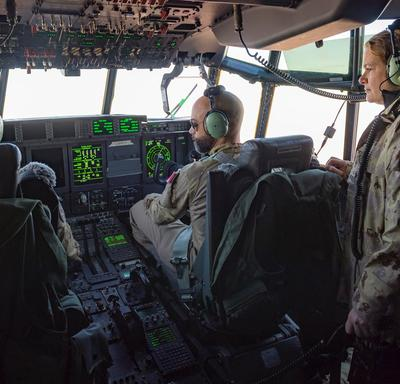 Governor General Julie Payette watches a pilot and his co-pilot at work in an aircraft cockpit.