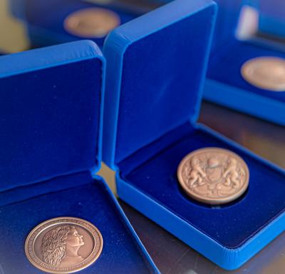 Three Governor General's Academic All-Canadian Commendation medal displayed in opened blue boxes on a table.
