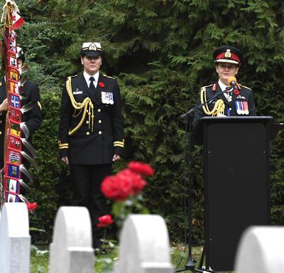 La gouverneure générale du Canada, en uniforme de l'armée canadienne, prend la parole à un podium, dans un cimetière, lors d'une commémoration du jour du Souvenir en Belgique. Son aide de camp féminin se tient à sa droite.