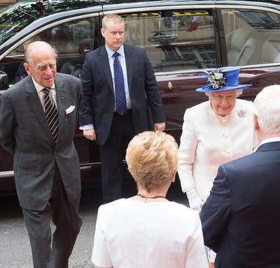 Her Majesty the Queen and the Duke of Edinburgh are greeted by Governor General Johnston and Mrs. Sharon Johnston. A bodyguard in a suit stands next to a vehicle in the background.