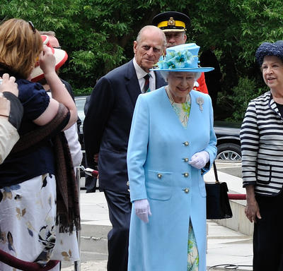The Queen and the Duke of Edinburgh walk outdoors, along a sidewalk beside a green lawn. The Queen waves. They are accompanied by several men in suits and military uniforms.