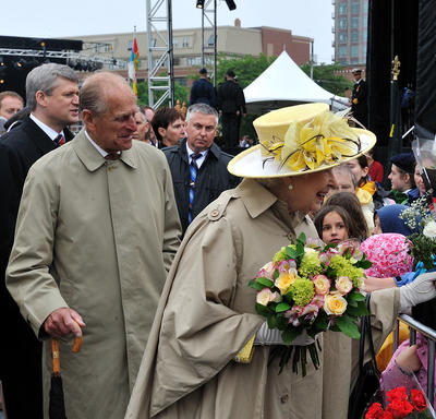 Her Majesty The Queen smiles as she receives a bouquet from a person in a crowd standing behind a barrier. The Queen holds more flowers in her other hand. The Duke of Edinburgh and Prime Minister Stephen Harper follow along behind her.