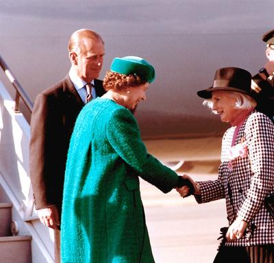 The Queen shakes hands with Governor General Sauvé, who curtsies. The Duke of Edinburgh is standing behind the Queen. A uniformed officer salutes in the background. All are standing at the bottom of a set of stairs extending from an airplane onto the tarm