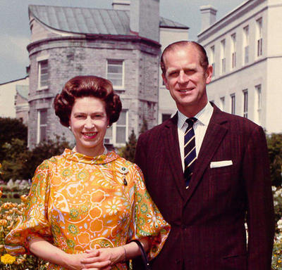 The Queen and the Duke of Edinburgh stand in the private gardens at Rideau Hall. They are both smiling. The Queen is wearing a yellow-and-orange-patterned dress; the Duke is wearing a dark suit.