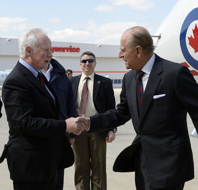 The Duke of Edinburgh shakes hands with Governor General David Johnston on the tarmac.