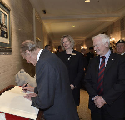 The Duke of Edinburgh writes in a large book as Governor General David Johnston looks on. The pair are in a lobby with other people.