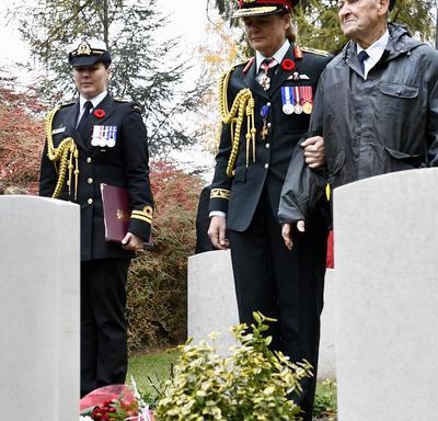 La gouverneure générale du Canada, en uniforme de l'armée canadienne, s'arrête devant une tombe dans un cimetière avec un ancien combattant à ses côtés.