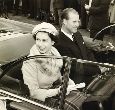 The Queen and the Duke of Edinburgh smile at the crowd while riding in an open-air vehicle. The photo is black and white.