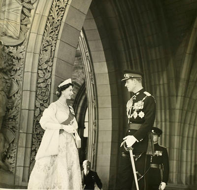 The Queen, dressed in a formal white ball gown and fur wrap, faces the Duke of Edinburgh, who is dressed in a military uniform. The two are standing in a stone archway carved with intricate designs.