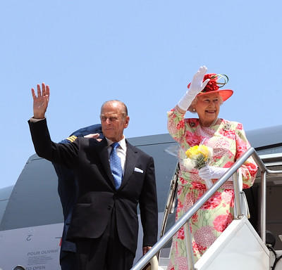 The Queen and the Duke of Edinburgh wave from the top of a white staircase. They are standing in front of the open door of an airplane.