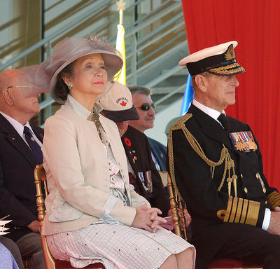 The Queen, Governor General Clarkson and the Duke of Edinburgh are sitting side-by-side at an outdoor event. Other dignitaries and guests are seated behind them.