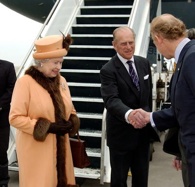The Duke of Edinburgh shakes hands with John Ralston Saul as The Queen and Governor General Clarkson look on. The group is standing on the tarmac at an airport, at the bottom of a set of stairs leading up to an airplane.