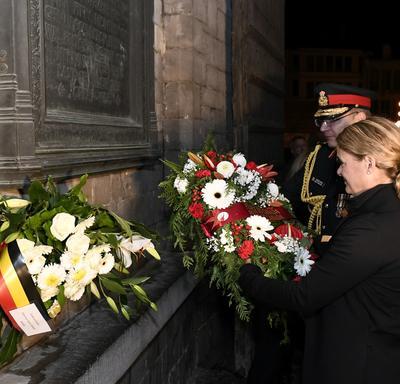 La gouverneure générale du Canada dépose une gerbe de fleurs devant un monument mural la nuit avec l'aide d'un militaire.