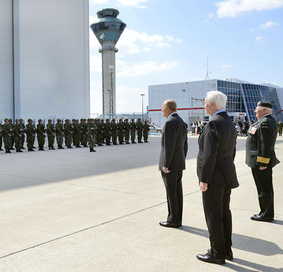 The Duke of Edinburgh and Governor General Johnston stand on the tarmac at an airport. They are facing a group of military members dressed in uniform and standing in formation. On their right, Colonel Joe Aitchison directs the group with an epée in hand.