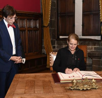 La gouverneure générale signe un livre d'or. Un grand homme se tient à sa droite et la surveille.