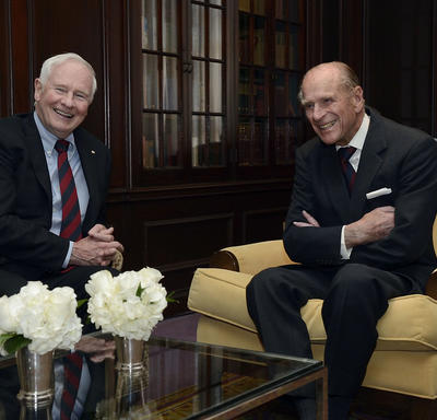 Governor General David Johnston is seated with His Royal Highness the Duke of Edinburgh in a sitting room. Both are smiling. Three vases of white flowers are on the table in the foreground and several shelves of books are in the background.