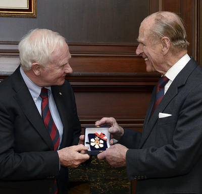 Governor General David Johnston hands a small box containing the insignia of the Order of Canada to the Duke of Edinburgh. The insignia is in the shape of a stylized white snowflake with a red maple leaf in its centre.