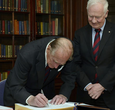 The Duke of Edinburgh signs a large book with gold-leaf edges as Governor General Johnston looks on.