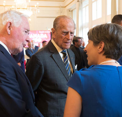 His Royal Highness The Duke of Edinburgh and Governor General David Johnston speak to a woman. They are in a large reception area with other guests in the background. A chandelier hangs from the ceiling.
