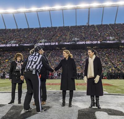 Governor General of Canada Julie Payette shakes hands with a referee at the 2018 Grey Cup Championship, in the centre of the field of the Commonwealth Stadium in Edmonton. The stadium is filled with fans.