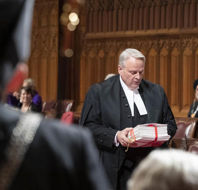 A senator approaches His Excellency with documents in hand.