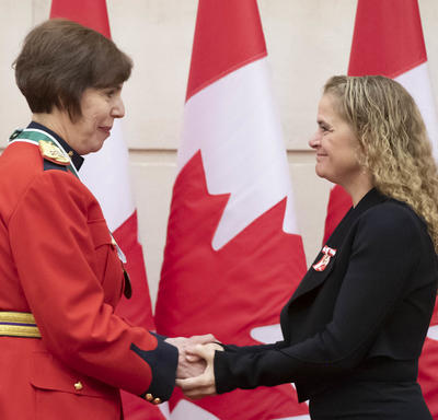 Shirley Cuillierrier is shaking hands with the Governor General.