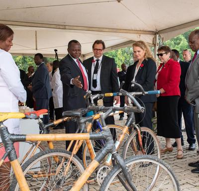 A crowd of people looking at bicycles.