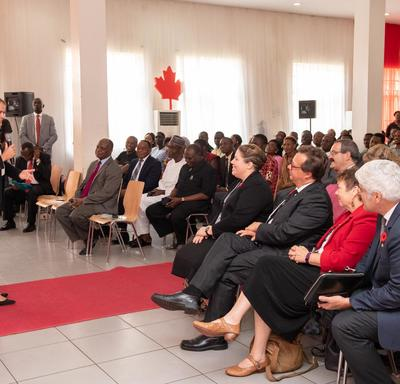 The Governor General speaks to a room of people. She is standing on a red carpet.