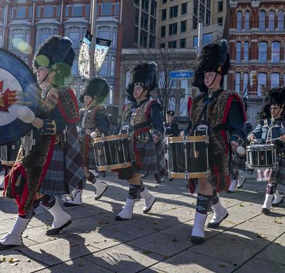 Drumers dresses in a military uniform comprised of a kilt and tartan march and play.