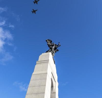 Five airplanes against a bright blue sky are flying above the National War Memorial.
