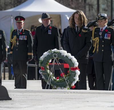 The Governor General salutes as she stand in front of a wreath.  Her son stands to her left.  Behind them is a row of people that includes the Chief of the Defence Staff, General Jonathan Vance.